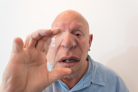 Older man looking over a large lens, distortion, bald, alopecia, chemotherapy, cancer, isolated on white, vertical aspect