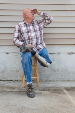 Smiling amputee man sitting on a stool, prosthetic leg crossed, shading eyes looking up, copy space, vertical aspect Stock Photo