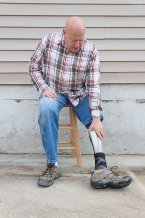 Amputee man on a stool reaching down to adjust prosthetic leg, copy space, vertical aspect