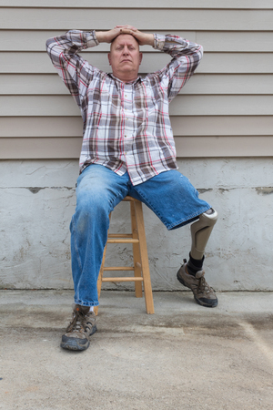 Amputee man sitting on a stool, prosthetic leg out, hands on head looking at camera, copy space, vertical aspect Stock Photo