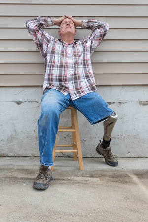 Amputee man sitting on a stool, prosthetic leg out, hands on head looking up, copy space, vertical aspect Stock Photo