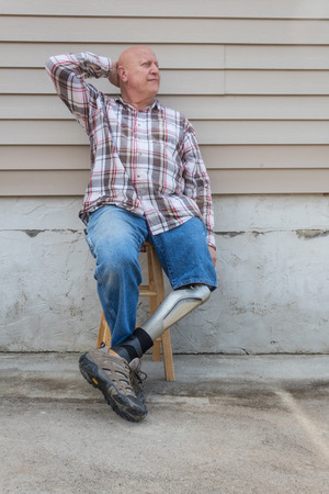 Amputee man sitting on stool with prosthetic leg crossed, had behind head, copy space, vertical aspect