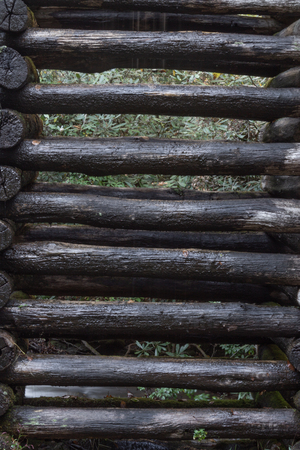Wet stacked logs supporting a mill sluice, Appalachian scene, vertical aspect Stock Photo