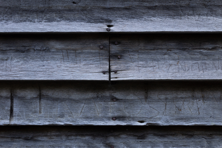 Wood clapboard siding on an old historic cabin showing defacing scratched grafitti, horizontal aspect