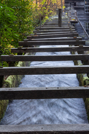 Low view of a wood walled sluice channeling water toward an old mill, vertical aspect Stock Photo
