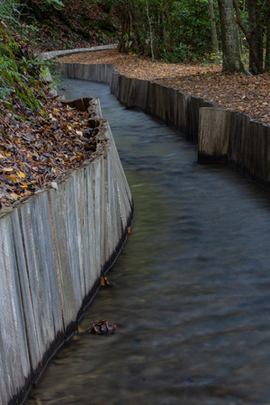 Wood walled sluice winding through wooded area leading to an old mill, vertical aspect