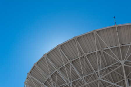 Very Large Array backlit sweep of radio astronomy observatory dish in clear sky, science technology space, horizontal aspect