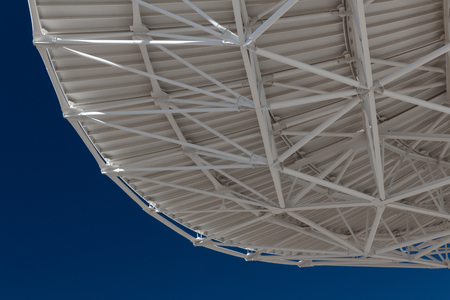 Very Large Array view from bottom of a radio satellite dish at the VLA against a deep blue sky, horizontal aspect