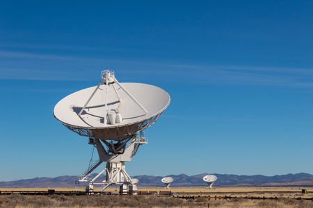 Very Large Array radio antenna dish close with others in distance, blue sky copy space, horizontal aspect Stockfoto