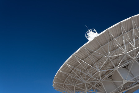 Very Large Array understructure of a radio telescope antenna dish pointing into a deep blue sky, copy space, horizontal aspect