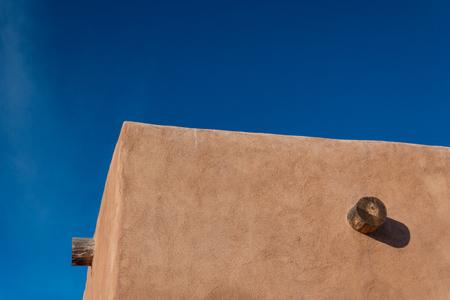 Red adobe exterior corner, exposed vigas, bright blue sky creative copy space, horizontal aspect