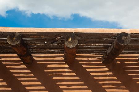 Creative cast shadows from vigas and latillas on exterior adobe wall, horizontal aspect Reklamní fotografie