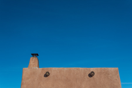 Exterior red adobe framed by blue sky, chimney and exposed beams, copy space, horizontal aspect
