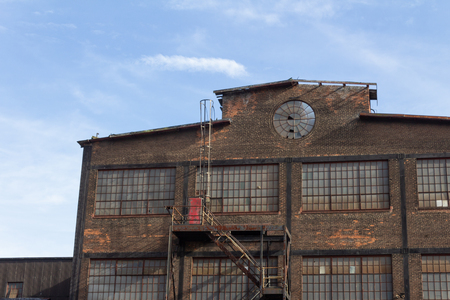 Profile of an abandoned industrial building, circular window in brick facade, horizontal aspect