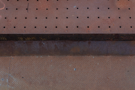 Background of perforated and woven metals, heavy rust patina, horizontal aspect