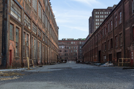 Street through a complex of derelict industrial buildings, daylight, horizontal aspect