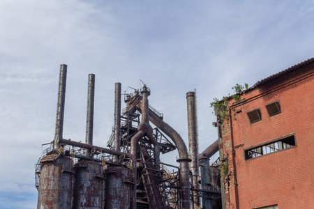 Stacks blast furnaces with rusting exterior, abandoned industrial landscape, horizontal aspect Stock Photo