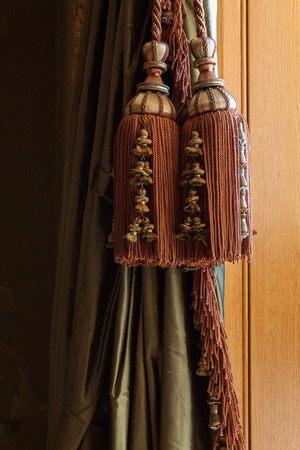 Elaborate large window curtain tie back tassels, cords, and trim over green silk curtains, warm wood background, vertical aspect
