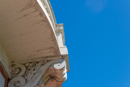 Architectural detail of wood balcony and carved corbel, blue sky copy space, horizontal aspect