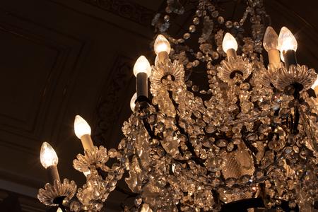 Cascade of crystals in antique chandelier, darkened room, horizontal aspect