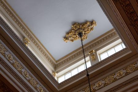Ceiling illuminated by clerestory windows to reveal elaborate cornice and frieze work, abundant gold leaf, horizontal aspect