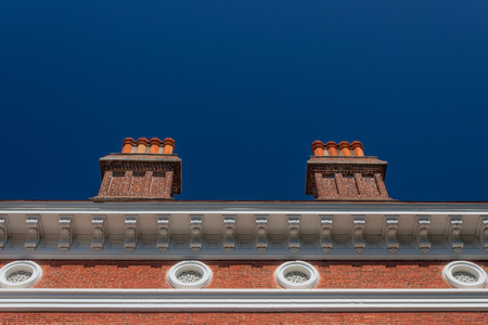 Formal centered exterior of a brick building with large chimneys and round windows, blue sky copy space, horizontal aspect