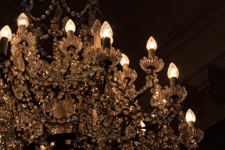 Beautiful chandelier with elaborate crystals in a dark room, horizontal aspect