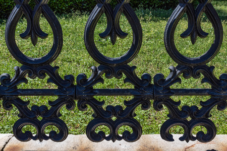 Detail of wrought iron fencing with green grass background, horizontal aspect