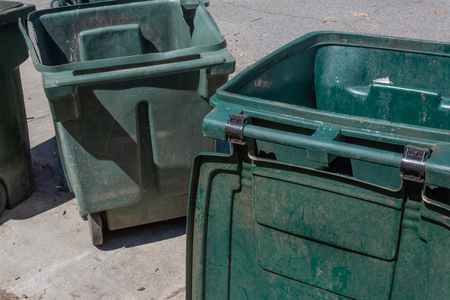 Large green trash cans, empty with lids open, curbside, horizontal aspect