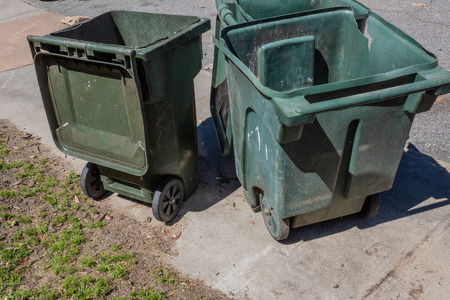 Three large green trash cans with lids open on a sidewalk, horizontal aspect