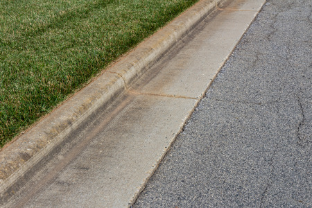 Angled view formed concrete curb, green grass and asphalt street, horizontal aspect 스톡 콘텐츠