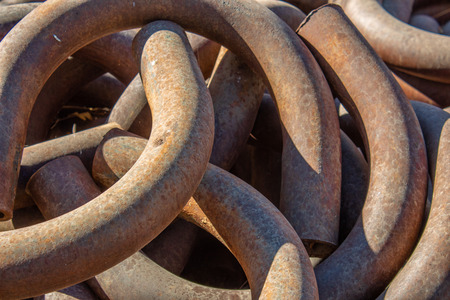 Background of curved, rusty metal pipes, horizontal aspect