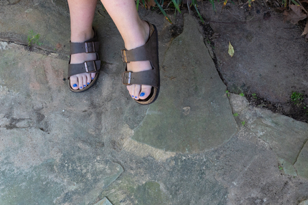 Feet of a woman in sandals with blue toenail polish against a stone ground, copy space, horizontal aspect