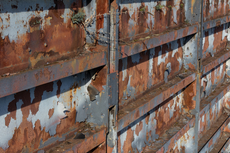 Steel wall background texture with corrosion, rust, and peeling paint, horizontal aspect