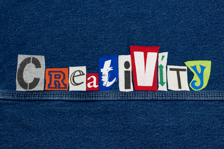 CREATIVITY word collage from cut out tee shirt letters, team innovation, horizontal aspect