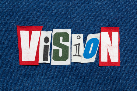 VISION word collage from cut tee shirt letters on denim, forward thinking, horizontal aspect Reklamní fotografie