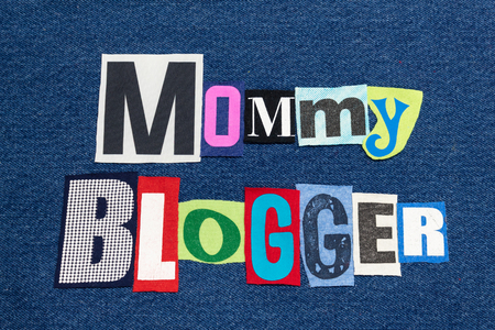 MOMMY BLOGGER text word collage colorful fabric on blue denim, parenting blogs and blogging, horizontal aspect Stock Photo