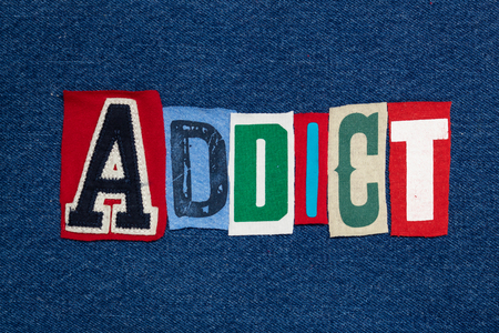 ADDICT text word collage, colorful fabric on blue denim, health and addiction concept, horizontal aspect