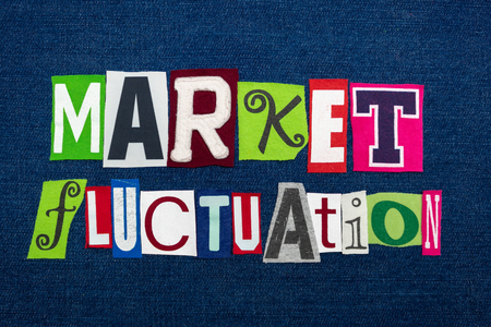 MARKET FLUCTUATION text word collage, multi colored fabric on blue denim, stocks price changes concept, horizontal aspect