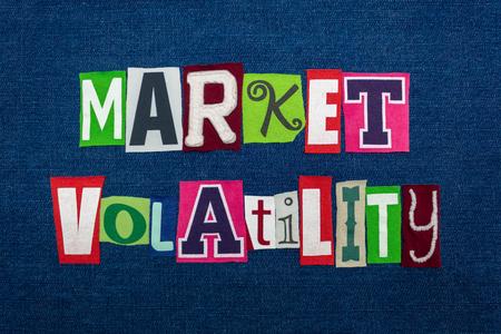 MARKET VOLATILITY text word collage, multi colored fabric on blue denim, unpredictable market direction concept, horizontal aspect Reklamní fotografie