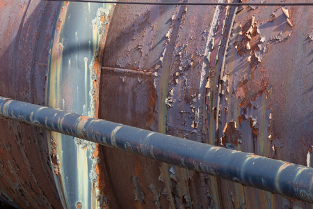 Sunlight across large and small pipes, rust and peeling paint textures, horizontal aspect