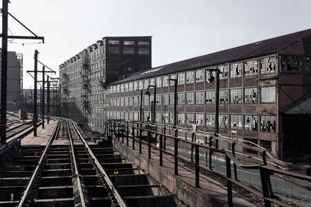 View down railroad tracks alongside abandoned industrial buildings, horizontal aspect