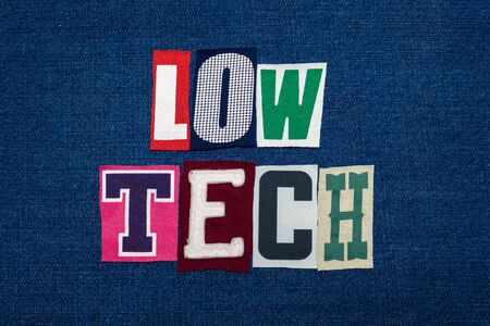 LOW TECH collage of word text, multi colored fabric on blue denim, easy technology concept, horizontal aspect