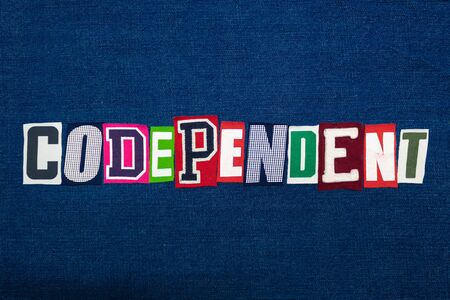 CODEPENDENT word text collage, multi colored fabric on blue denim, mental health concept, horizontal aspect