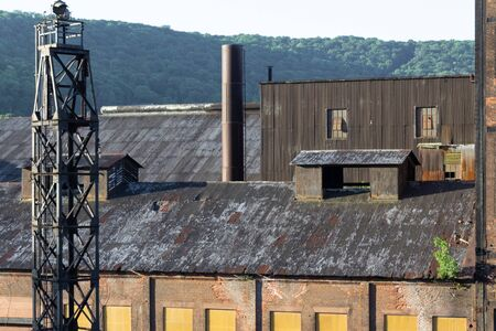 Elevated view of manufacturing warehouse buildings of brick and corrugated metal, mountains behind, horizontal aspect