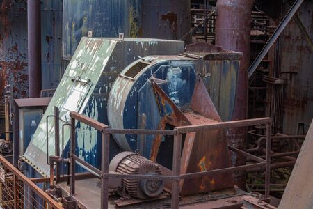 Machinery on exterior of an old steel manufacturing plant, heavy rust and paint patina, horizontal aspect