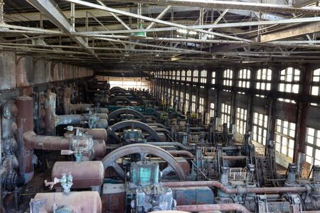 Rows of vintage machinery in an old steel manufacturing plant, horizontal aspect
