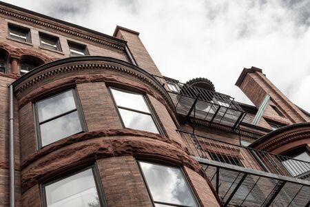 Detalles de molduras dentadas y piedra rústica en el antiguo edificio de apartamentos de piedra rojiza exterior, aspecto horizontal