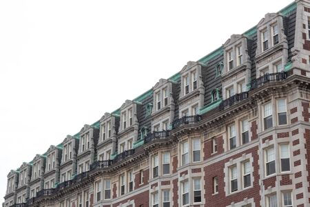 Ornate mansard roof style apartment building with brick face, green oxidized copper flashing details, horizontal aspect Foto de archivo