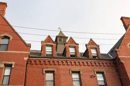 Fachada de ladrillo rojo en edificio de apartamentos urbanos residenciales con buhardillas y cúpula, aspecto horizontal